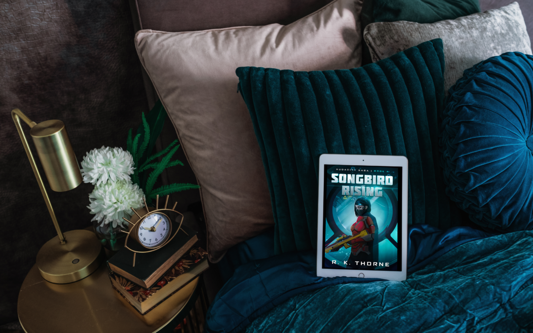 Cover of SONGBIRD RISING on tablet on a luxurious blue velvet bed